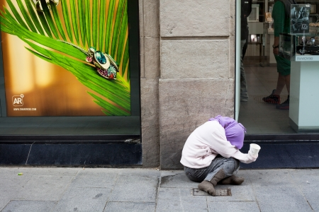 A beggar is sitting in front of a swarovsky-shop in the Rambla-Street in Barcelona  Hiding his head   He has a plastic cup in his hand