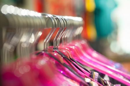 tienda de ropas: Breve enfoque de la imagen de percha para la ropa. Colgando en una fila.
