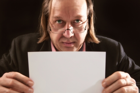 A blonde long haired manager hod a blanc paper in his hand.picture is made with high contrast. photo