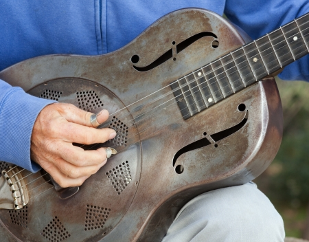 A detail picture of a guitar playing man with a metal - guitar