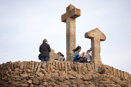 distant spot: people standing on the view point in park guell . watching the city from above.