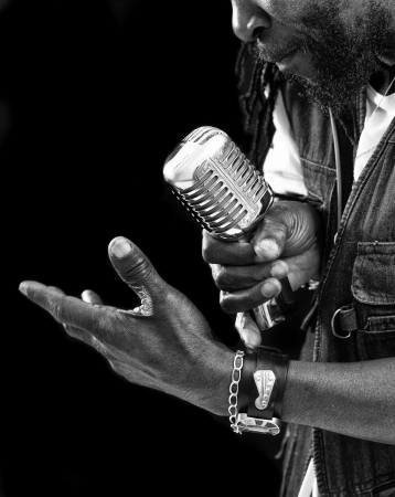 A closeup of a rasta singer with a chrome microphone.Picture is black and white Stock Photo