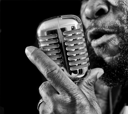 old black man: A closeup of a rasta singer with a chrome microphone Picture is black and white