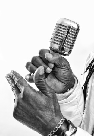 A closeup of a rasta singer with a chrome microphone  icture is black and white Stock Photo