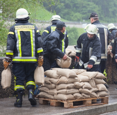 A few fireman are helping by floodwater. They carry sandbags to stop the flood on a river.