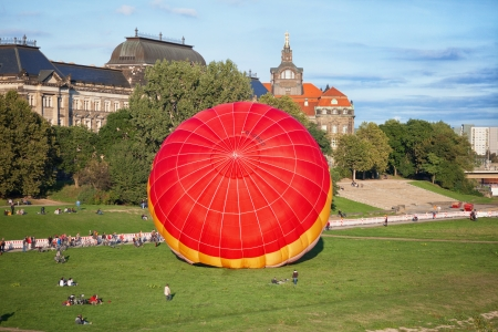 A starting balloon on the riverside Elbe in dresden. Alot of people looking at the starting Balloon.