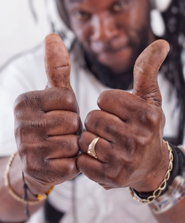 A rastafari show two thumbs up .Focus on thumbs photo