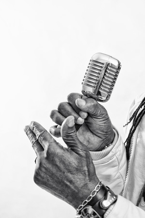 Hands of a black singer hold a microphone in his hand Stock Photo