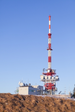 A red white Radio mast on a mountain in the Alps