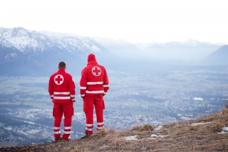 Salzburg , Dezember 30.2013. Two red Cross helpers in the austrian mountain are waiting to help a Paraglider in need.  Dezember 30, 2013 in Salzburg Gaisberg