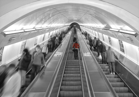 A women in red is the only one sharp on a escalator between other people in motion.