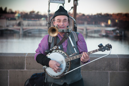 he is different: Prag , Czechoslovakia - februar 17 . 2014 : A solo entertainer makes music on the charles bridge in prague. He plays different kinds of instruments. People can listen