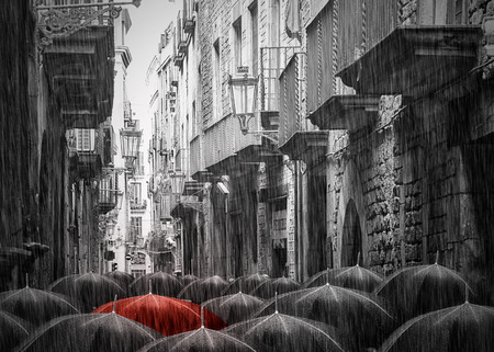 Black and white picture. A lot of umbrellas in the same style in a rainy street in Barcelona. Picture is toned. One Umbrella is red.