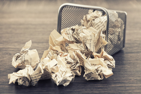 wastepaper basket: A lot of wrinkled paper laying in and around a wastepaper basket.picture is toned.