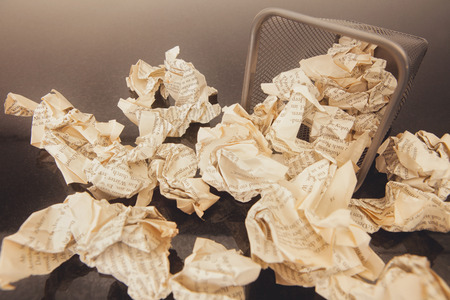 A lot of wrinkled paper laying in and around a wastepaper basket.picture is toned.