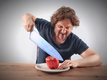 A mad looking man try to cut a red healthy pepper with a very big knife photo
