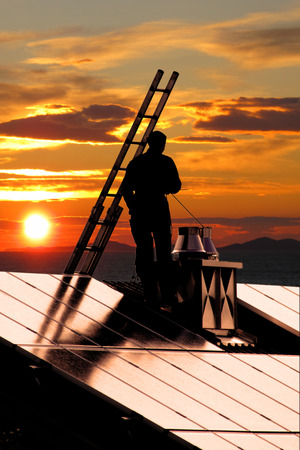 cleaning up: chimney sweeper on sunset standing on a roof with a photovoltaik. Stock Photo