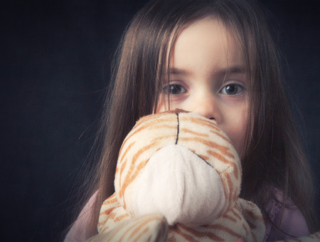 cuddly toy: A young girl hold her cuddly toy