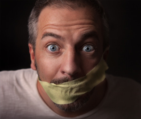 A gagged man is stearing in the camera with big blue eyes. Picture is toned. photo