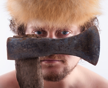 ax man: man with blue eyes is looking trough a ax. Stock Photo