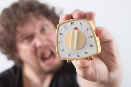 affraid: Astonished and affraid man show a egg timer. Picture is toned. Stock Photo