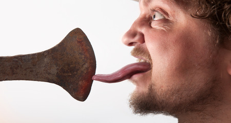 ax man: A profile photo of a man licking on a ax. Dodge and burn picture. Stock Photo
