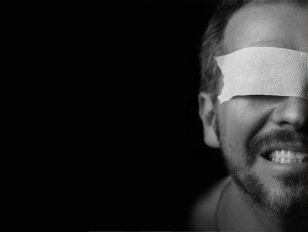 Half portrait of a blindfolded man. Pictur eis black and white photo