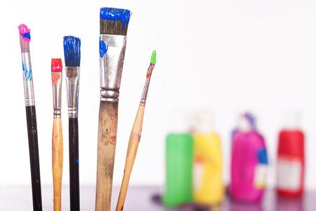 brocha de pintura: Algunos cepillos con colores delante de paleta de colores. Aislado en blanco. Foto de archivo