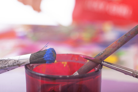 Some brushes with colores in front of colored pallet. photo