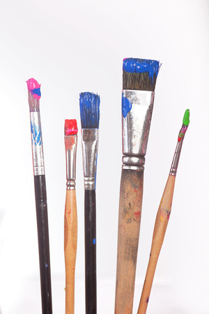 Some brushes with colores in front of colored pallet. Isolated on white. photo