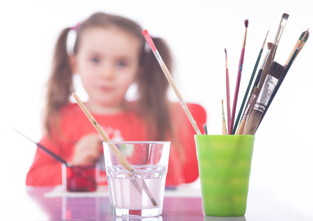 Picture of colorful painting utensils .The Girl in the background is unsharp. Short focus picture. Bokeh. photo