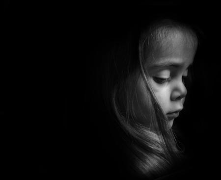 mirada triste: Baja clave Retrato de un ni�o peque�o. Chica de mirada triste que est� buscando down.Picture es blanco y negro.