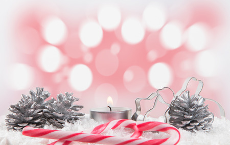 candy stick: Christmas decoration with candy stick and candle. Light bokhe in the background. Picture is toned. Fir cones lay byside.