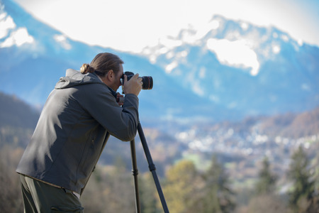 outdoor photo: Photgrapher is  taking picture of a mountain. The mountain is unsharp . Focus on photographer.You see the man from behind.