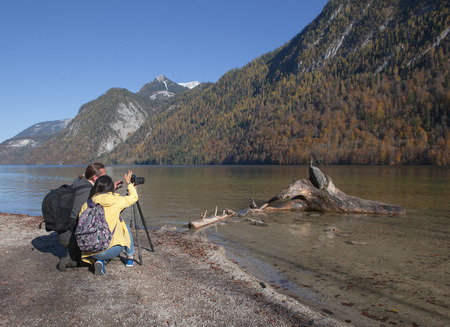 Couple is taking a picture of a trunk in the water.Picture is made on a sunny autumn day .The driftwood is laying near the riverside. photo