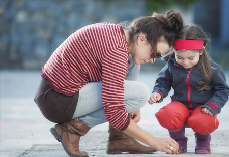 children painting: Mother and daughter are painting on the street.Picture is toned.