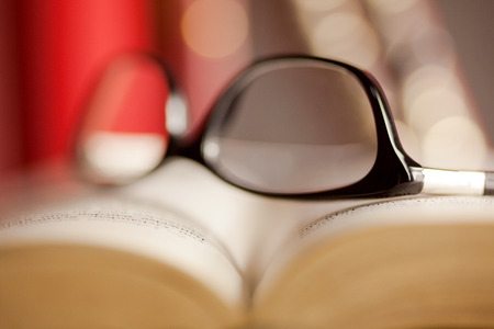 cramming: Glasses are laying on a book . Short focus picture. Focus on glasses.Books in th e Background are unsharp.