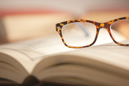 Glasses are laying on a book . Short focus picture. Focus on glasses.Books in th e Background are unsharp. photo