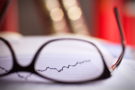 Glasses are laying on a share index.index i going up. Show positive performance. picture is toned photo
