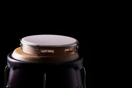 Tambourine laying on a bongo drum. Isolated on black. picture  with side light. photo