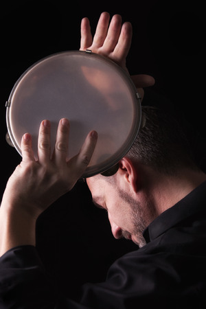 A musician is holding a tambourine in his hands. Low key picture with stripe light. photo
