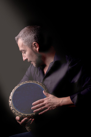 shaking out: A musician is holding a tambourine in his hands. Low key picture with stripe light.
