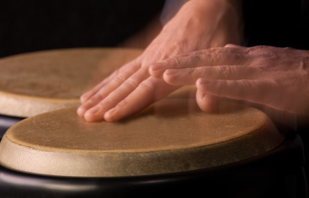 motion picture: Motion Picture of a bongo Player. Black background.Picture is toned.