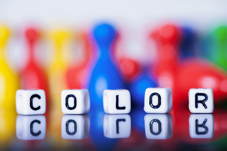 Cube Letters showing color  in front of  many unsharp ludo figures. photo