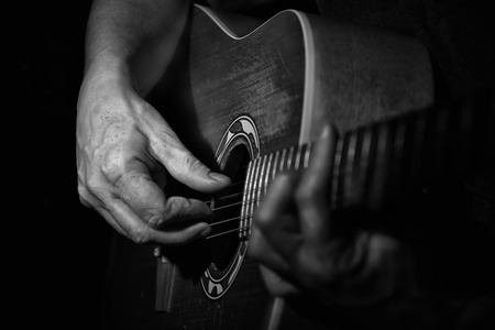 adulation: Black and white Picture . Close up of a guitarplayer . The Hand of the player looking aged. High contrast.