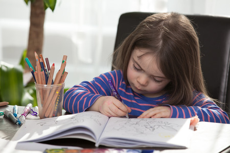interested: A young Child is Painting on a coloring book. The young girl is looking very interested in drawing.