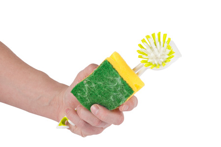 A caucasian hand is holding a yellow green  sponge and a brush in his hand. Isolated on white. photo