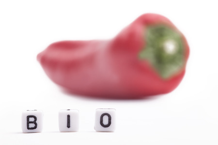 organic peppers sign: Cube Letters show Bio  in Front of unsharp re pepper on white background.
