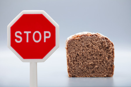 carb: A stop sign near a slice of a granary Bread on gray background. Low carb eating.
