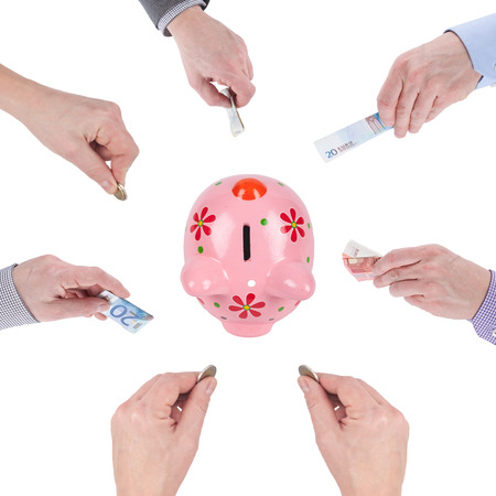Many Caucasian Hands give money to a piggybank. Crowdfunding methaphor.